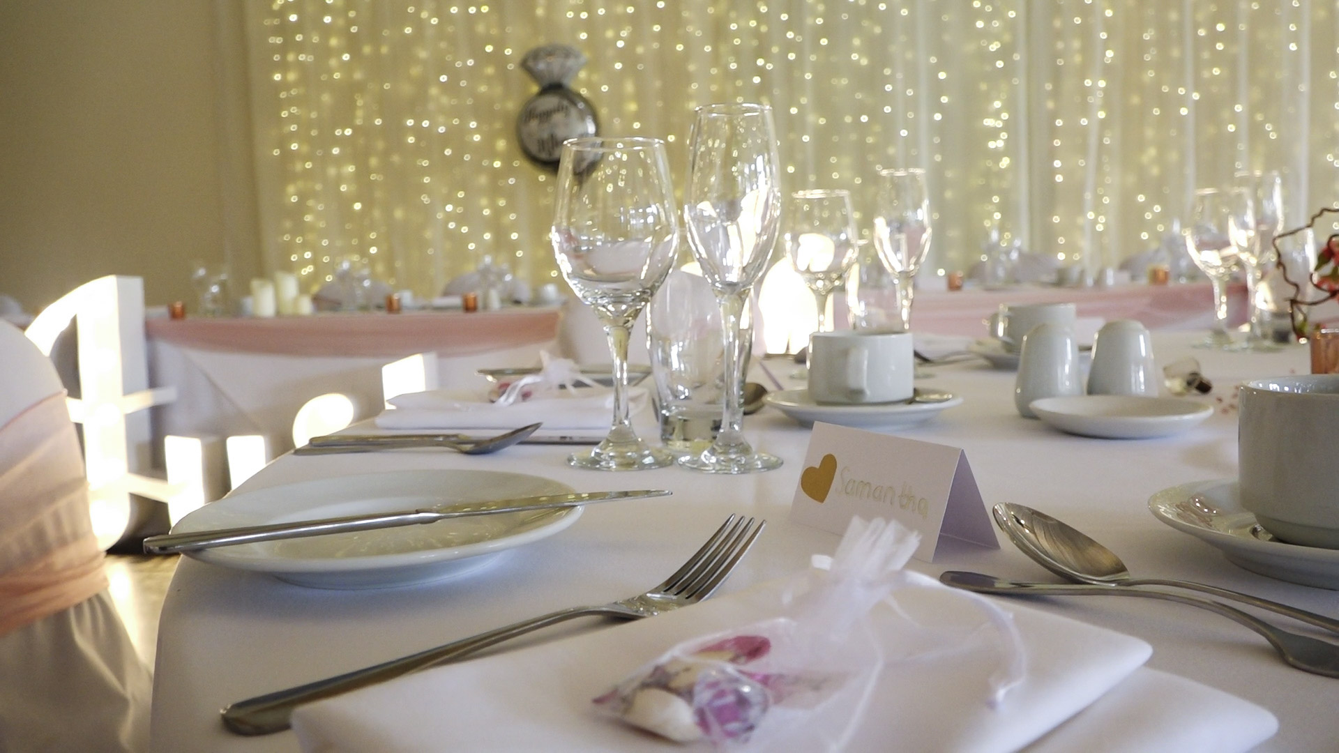Beamish Hall wedding decor - tables set with soft blush and dinnerware. A blanket of fairy lights can be seen in the background